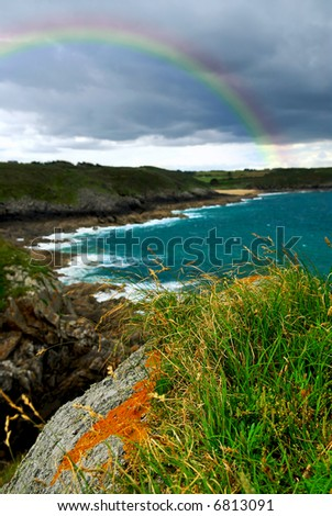 Landscape of rocky Atlantic coast in Brittany France with stormy sky and rainbow. Shallow DoF with focus on foreground grass. - stock photo