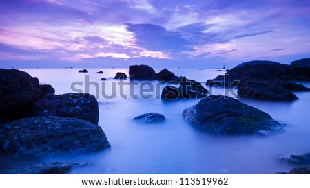 Landscape of sea with dramatic wave and rock in sunset. - stock photo