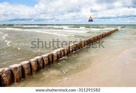 Landscape of sea with waves and cloudy sky. Breakwater and warning sign in the foreground. Baltic sea coast near Leba in Poland. - stock photo