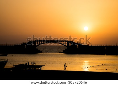Landscape of the sunset at Montaza beach , in Alexandria - Egypt , showing a bridge , with a man who is fishing