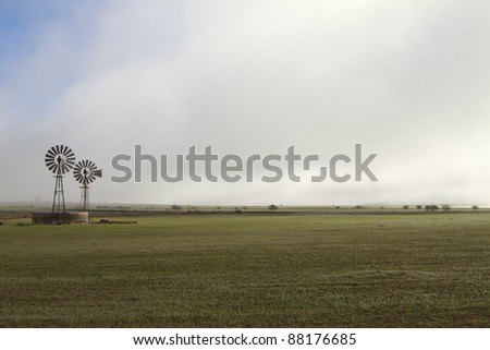 Landscape of two wind pumps against white clouds - stock photo