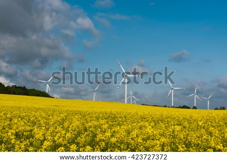 Landscape of windmills producing energy on a yellow rape field with view of the beautiful sky with clouds - stock photo