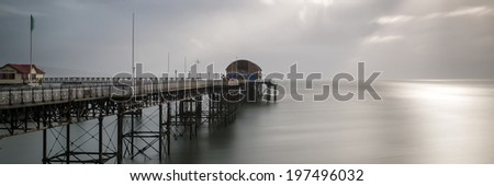 Landscape panorama long exposure moody image of Mumbles pier in Wales - stock photo