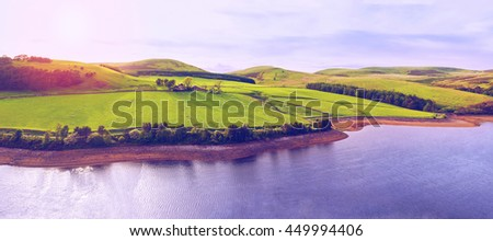 Landscape panoramic view of green valley, hill, river and cloudy blue sky with sunset. Pentland hills, Scotland - stock photo