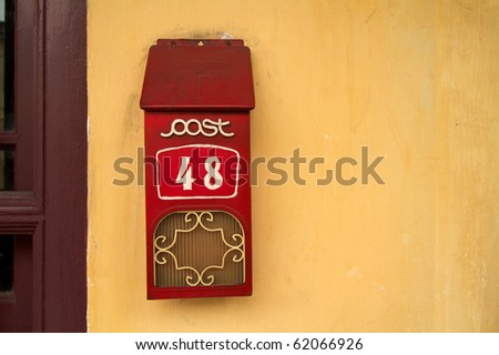 Landscape photo of retro letterbox against yellow wall - stock photo