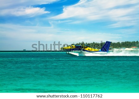 Landscape photo of Sea plane flying above ocean - stock photo