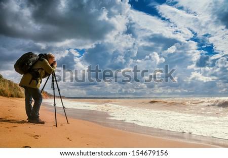 Landscape photographer makes sea shoots on the deserted beach - stock photo