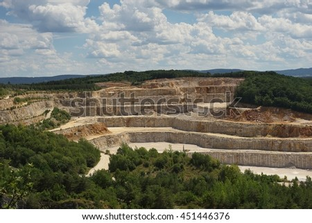 Landscape Picture on the deep opencast stone mine, quarry or surface, strip mine. Big mine for raw material extraction of limestone of calcite stone. Raw material for production of cement or concrete. - stock photo