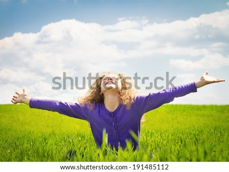 Landscape, picture, portrait very emotional, happy little girl with arms outstretched, looking up to blue sky meadow sunny day, isolated background green grass, clouds. Positive human emotion reaction - stock photo