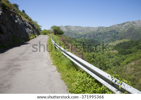 landscape rural grey lonely road between green mountains in countryside of Asturias Spain Europe - stock photo