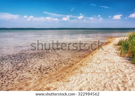 Landscape - sandy beach, clouds over lake with clear water and sandy bottom - stock photo