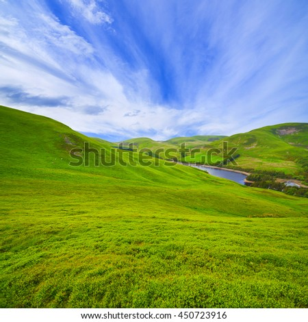 Landscape scenery of green valley, hill, river and cloudy blue sky. Pentland hills, Scotland