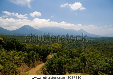 Landscape showing two El Salvador volcanoes and the village of Juayua. - stock photo