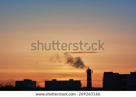 Landscape - silhouettes of rooftops and sky at sunrise with clouds - stock photo