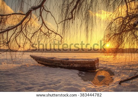 Landscape.sunrise,frozen lake, old snowy boat - stock photo