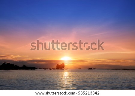 Landscape: The beautiful sunset above the sea and Silhouette building on the sea.
