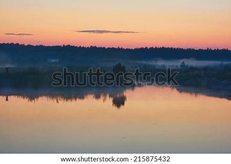 Landscape - Twilight on the lake, the forest in the background and fog on the coast