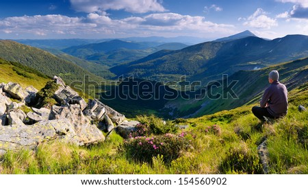Landscape view of a summer day with a tourist in the mountains - stock photo