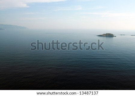 landscape view of an island on a blue sea - stock photo