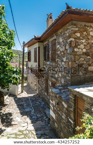 Landscape view of historical Doganbeyli village in Aydin, Turkey with historical small stone houses on bright blue sky background.