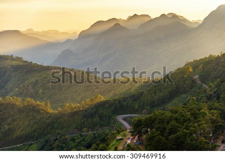 landscape view of mountain , tent , road in forest with sunset scene  - stock photo