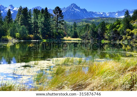 landscape view of the lake and snow covered mountains in the colorful alpine scenery during foliage season - stock photo