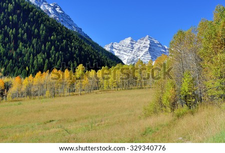 landscape view of the snow covered mountains with colorful yellow aspen during foliage season in Colorado