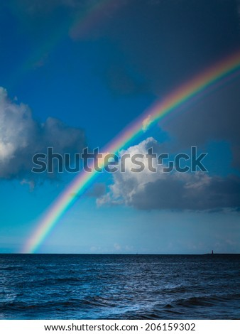 landscape view on cloudy sky with colorful rainbow at sea or ocean outdoor. Weather. - stock photo