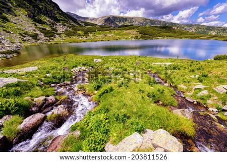 Landscape with a glacial lake in the highlands of Fagaras mountains, Romania - stock photo