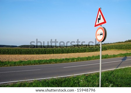 Landscape with a traffic sign: Don't overtake because of curves.