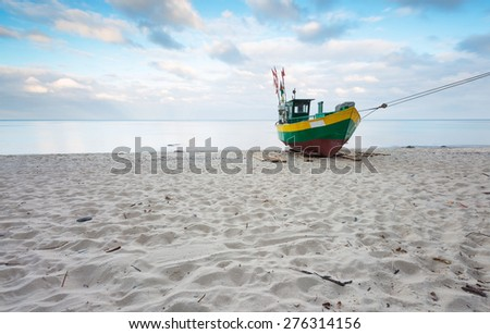 Landscape with Baltic Sea. Fishing boat on the beach. Tranquil evening landscape. Long exposure photo