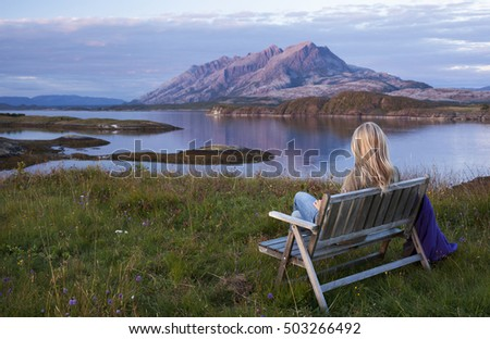 Landscape with blond woman sitting on bench, enjoying view over islands and mountains at beautiful summer evening after sunset. Photographed in Helgeland, Norway.