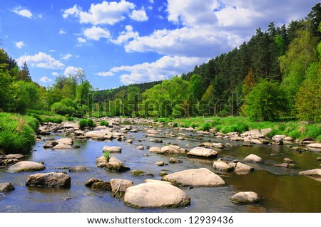 Landscape with calm river with stones, vivid green forest banks and bright blue sky. - stock photo