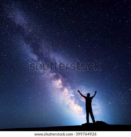 Landscape with colorful Milky Way. Night sky with stars and silhouette of a happy man with raised up arms on the mountain. Beautiful Universe. Space background - stock photo