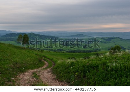 Landscape with country road to the valley in the spring foothills at fields with green grass of Altai mountains under sunset cloudy sky, Siberia, Russia - stock photo