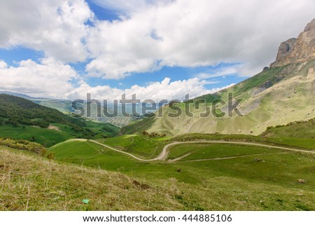 Landscape with dirt road in the mountains under cloudy sky - stock photo