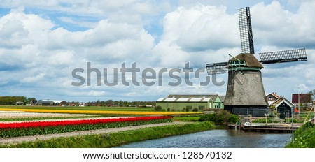 Landscape with Dutch windmill and colorful field of tulips in Holland. Panorama - stock photo