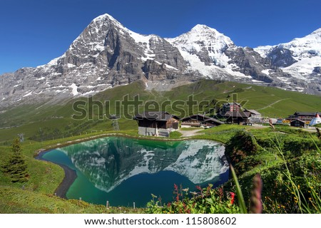 Landscape with Eiger, Moench and part of Jungfrau (to the right), in the Swiss Alps (Bernese Alps) reflecting in a pond at Kleine Scheidegg. - stock photo