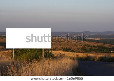 Landscape with empty billboard in the middle - stock photo