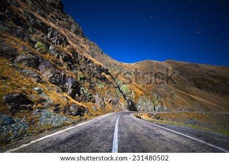 Landscape with empty road at night in the mountains, under clear sky with stars - stock photo