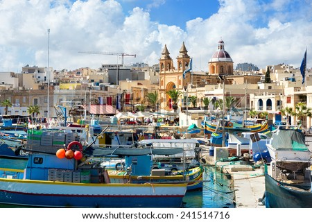 Landscape with fishing boats and pier in Marsaxlokk harbour. Malta - stock photo