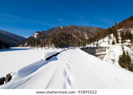 Landscape with foot tracks on a dam frozen lake in the mountains