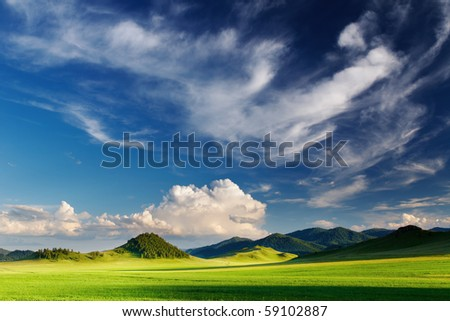 Landscape with green field and blue sky