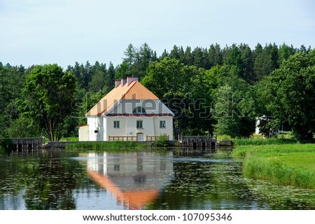 Landscape with houses and a  forest on coast of a pond - stock photo