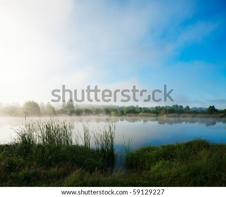 Landscape with lake and a morning fog - stock photo