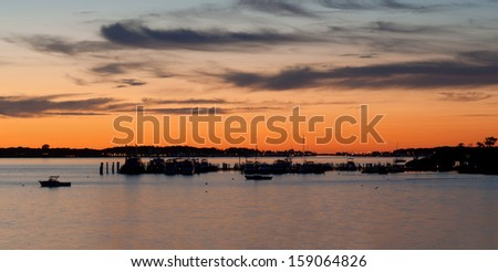 Landscape with lake, silhouettes of boats and sunset sky at Lake Montauk, New York, USA - stock photo
