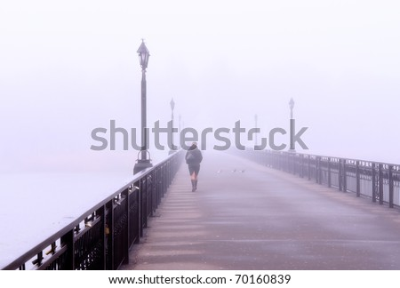 Landscape with  lonely lady crossing a bridge in the misty morning - stock photo