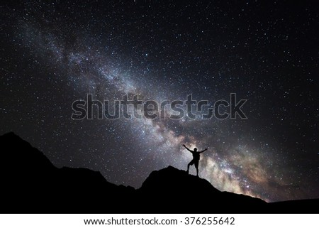 Landscape with Milky Way. Night sky with stars and silhouette of a standing happy man with raised up arms on the mountain. - stock photo