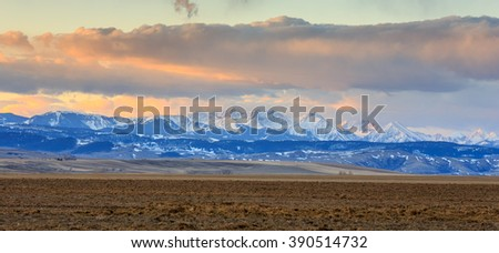 Landscape with mountains, peaks, farmland, and clouds.