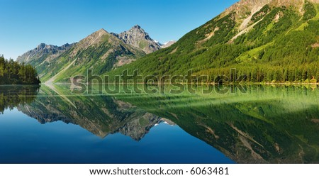 Landscape with mountains reflected in quiet lake - stock photo